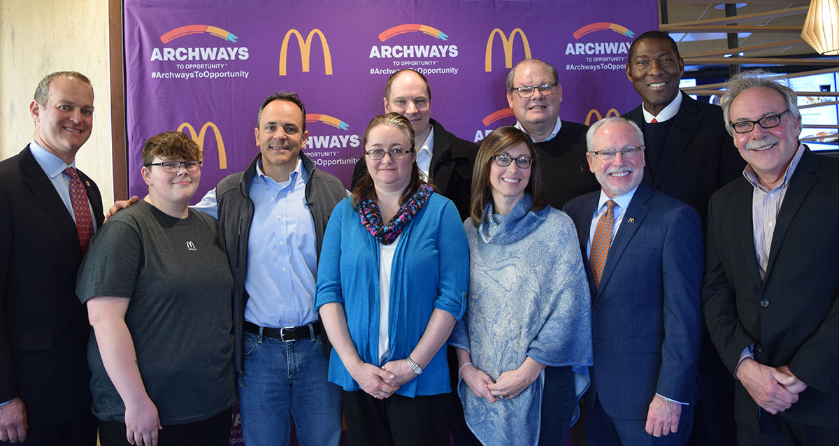 People pose in front of McDonald's Archways to Opportunity Banner