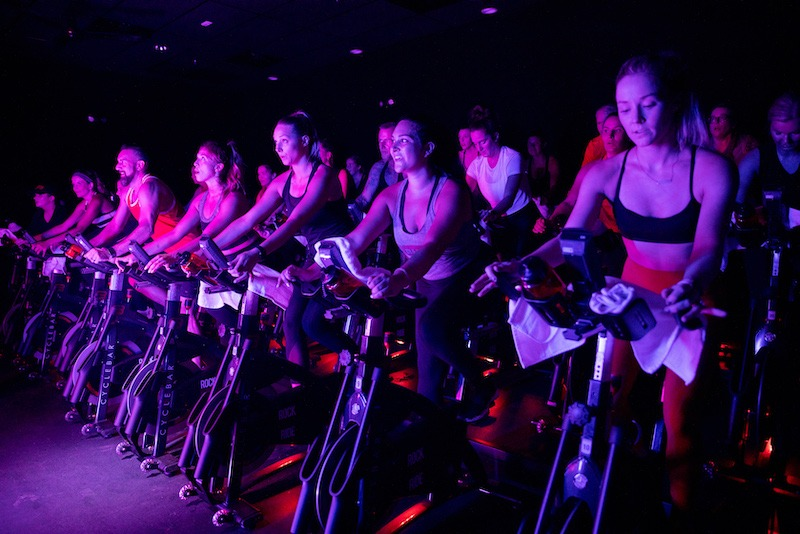 Men and women in workout clothes on stationary bikes at CycleBar in Tennesee